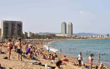 people on a beach in barcelona in june