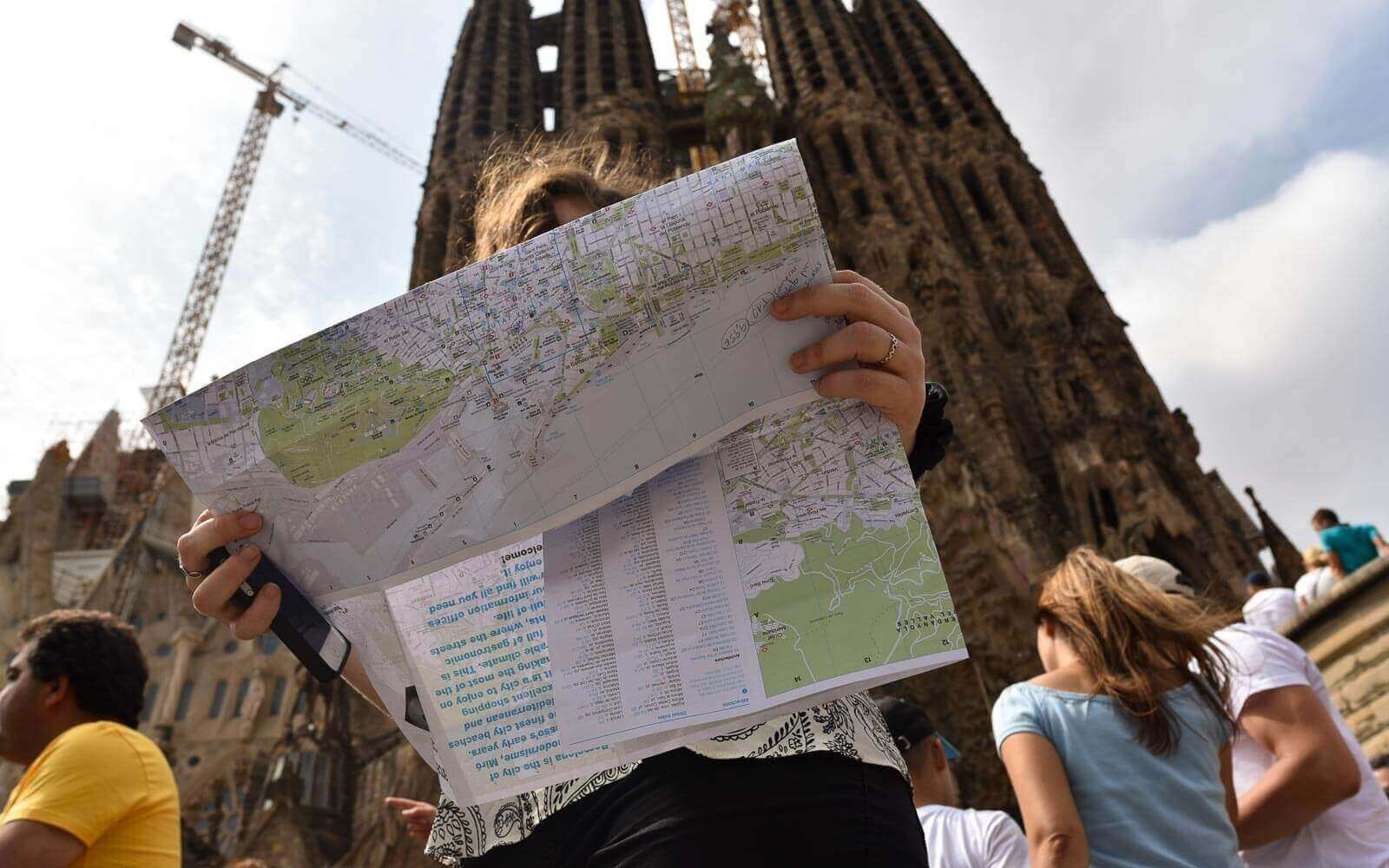 a woman reading a barcelona map in front of sagrada familia