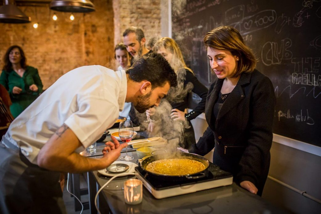 a tourist makes paella at a cooking workshop in barcelona