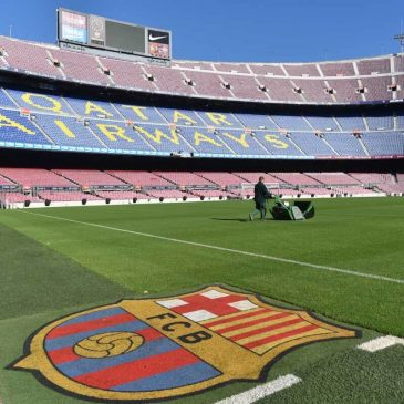 the barcelona fc logo painted on the grass at field level at camp nou stadium barcelona