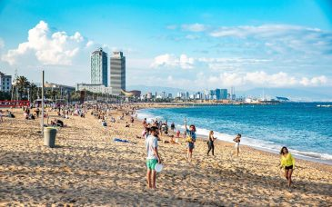 locals play frisbee and volleyball on one of barcelona's most popular beaches