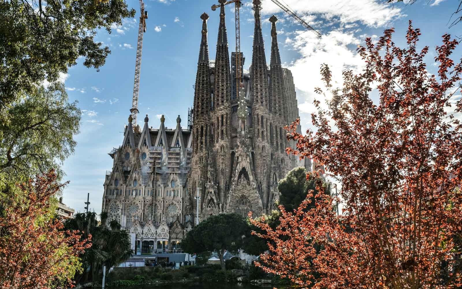 the nativity façade of sagrada familia from across the pond at dusk in barcelona
