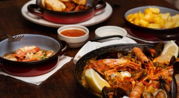 a paella set menu with patatas bravas and garlic prawns at bodega joan barcelona spain