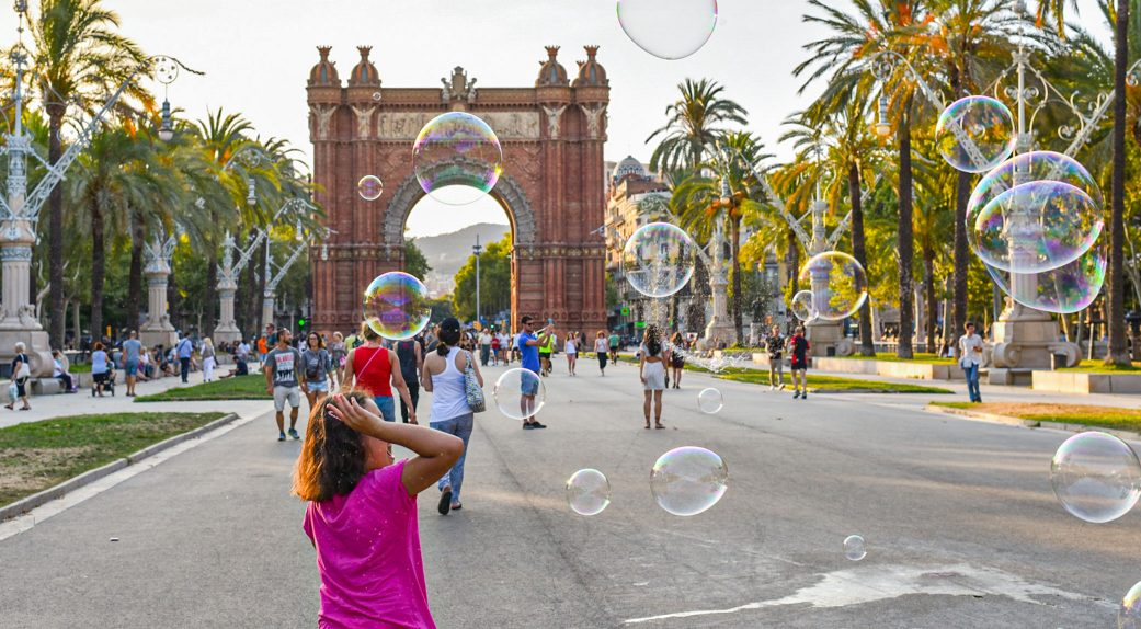 a child plays with bubbles in front of the arc de triomf in barcelona spain